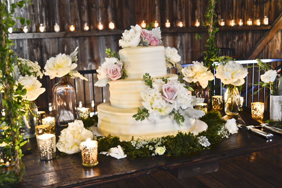Rustic Wedding Cake in barn with pink flowers and gold accents