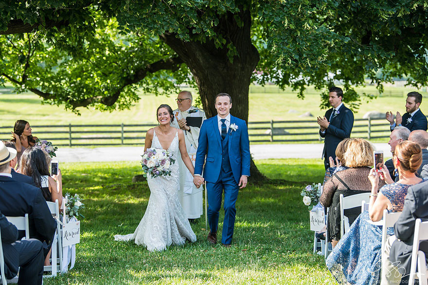Bride and Groom Walk Down Aisle in Front of Scenic Tree at Springton Manor Farm